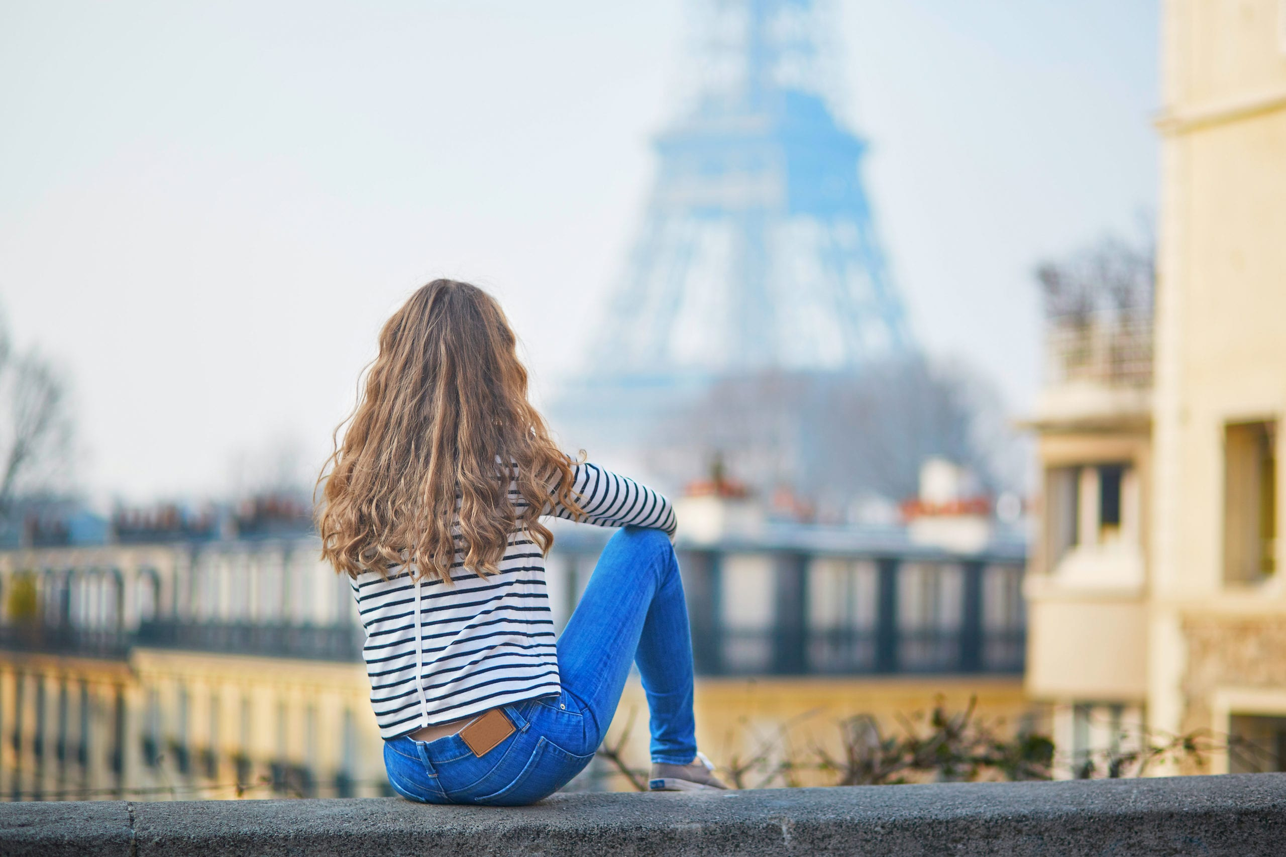 Beautiful young girl outdoors near the Eiffel tower, in Paris
